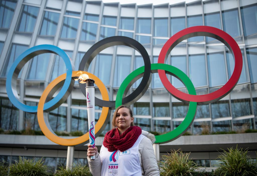 Flamme Olympique devant les anneaux et le CIO