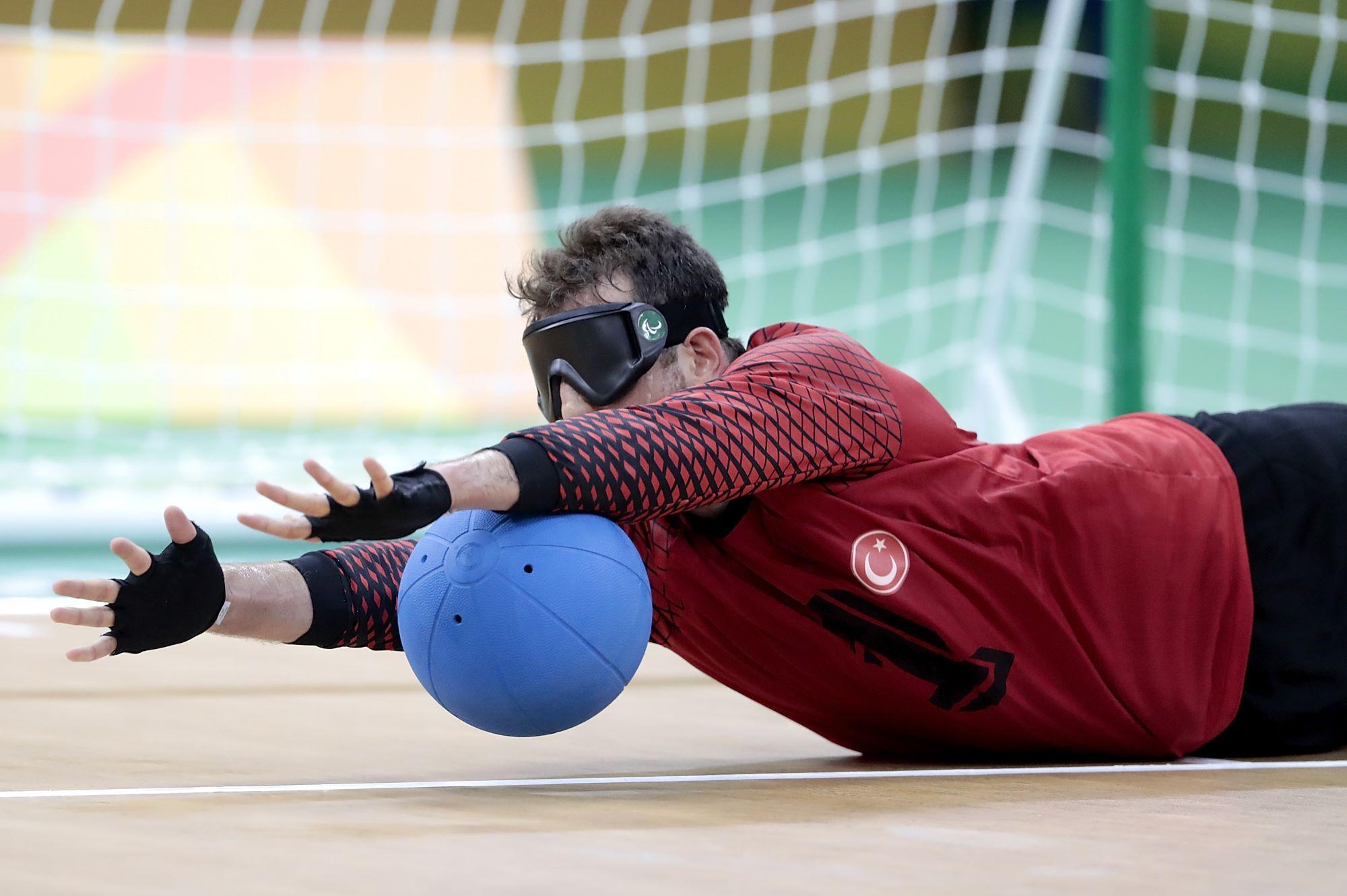 Un joueur de goalball arrête le ballon en se couchant au sol, les bras tendus