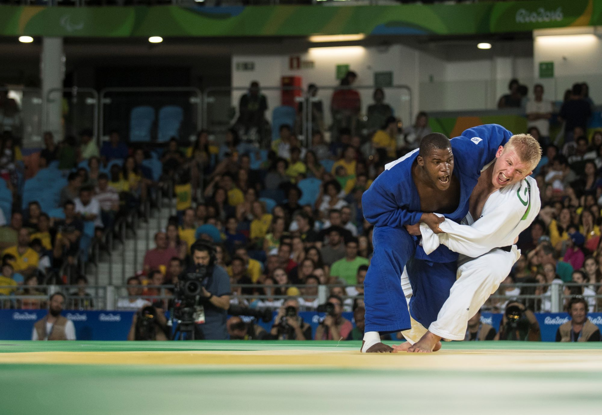 Un judokat avec un kimono bleu empoigne un judoka en kimono blanc lors des Jeux Paralympiques de Rio 2016