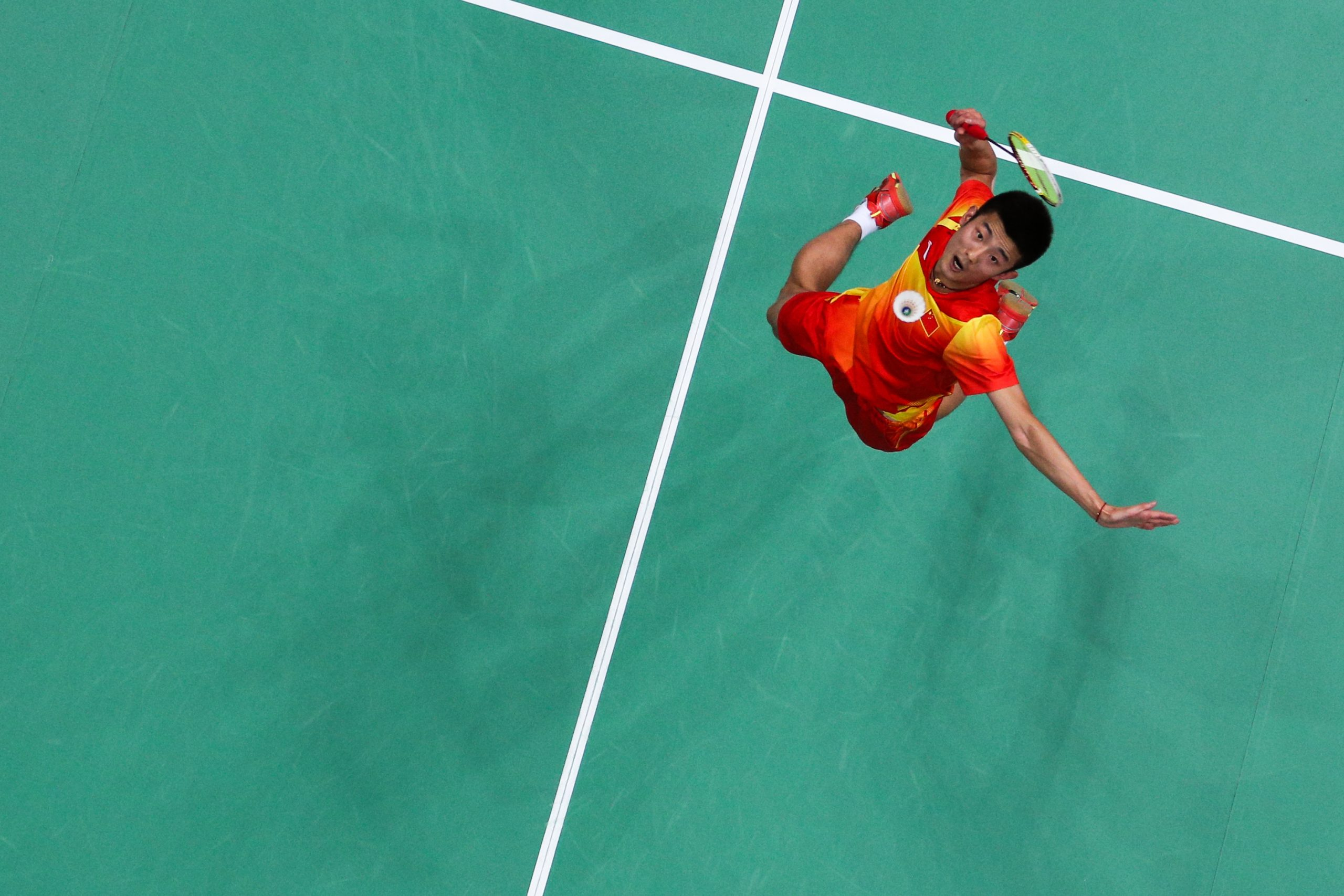 Joueur de badminton vu d'en haut en train d'exécuter un smash.