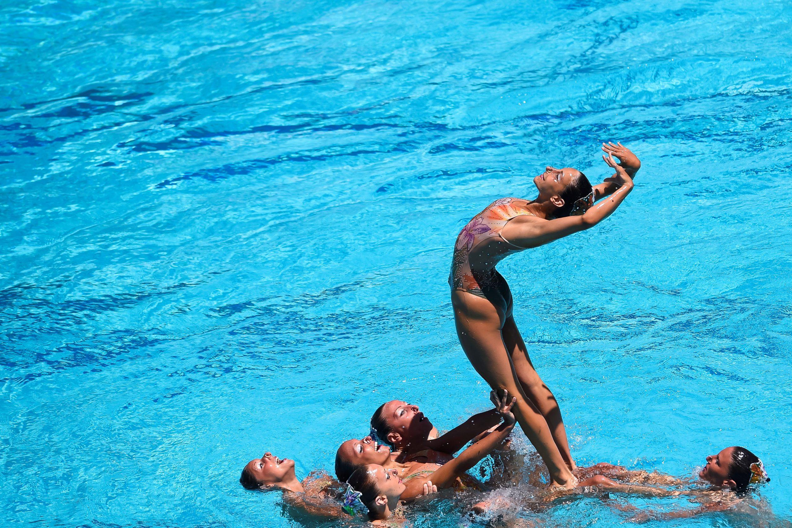 Nageuse en train d'être soulevée au dessus de l'eau par ses coéquipières.