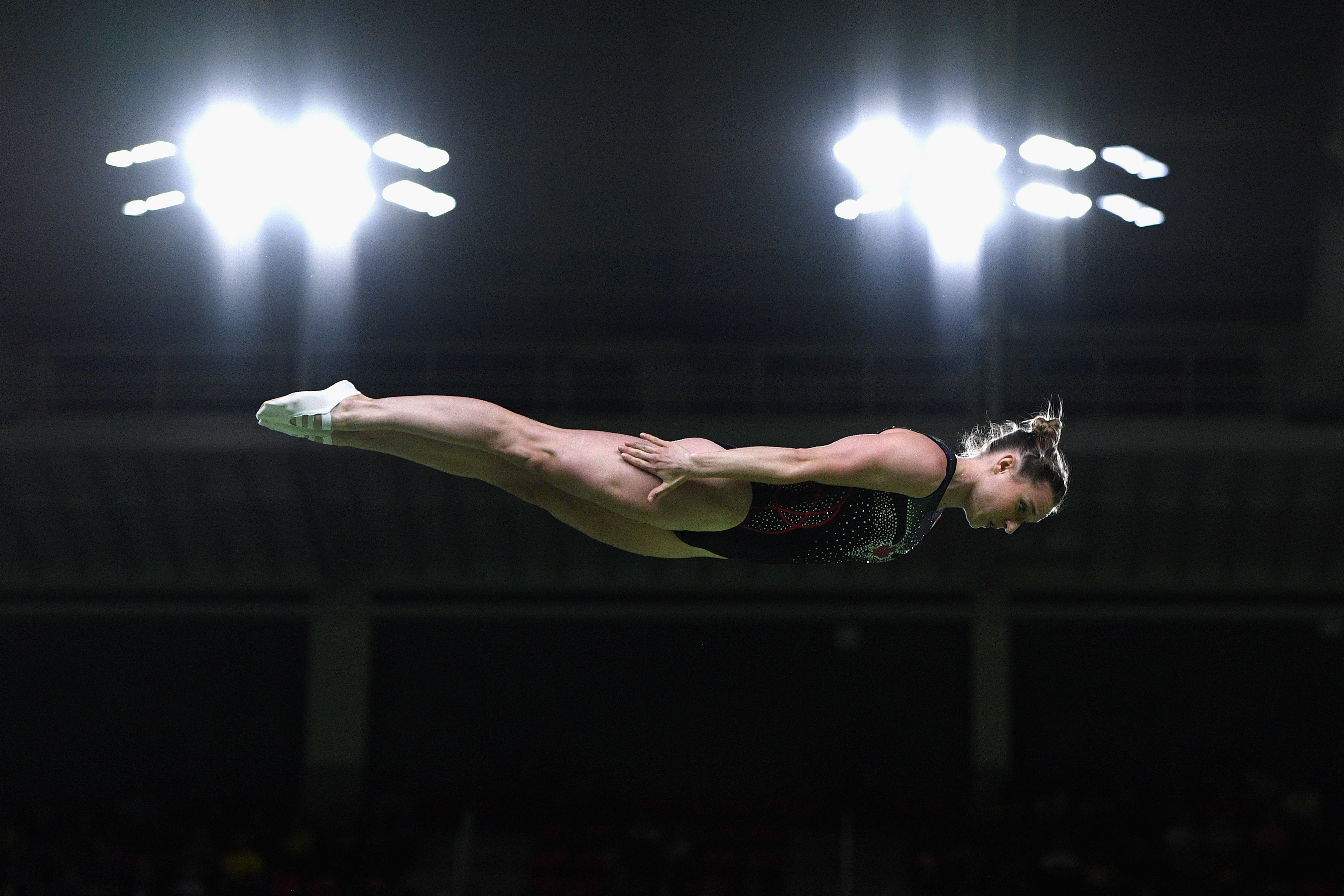 Une athlète en pleine figure de trampoline.