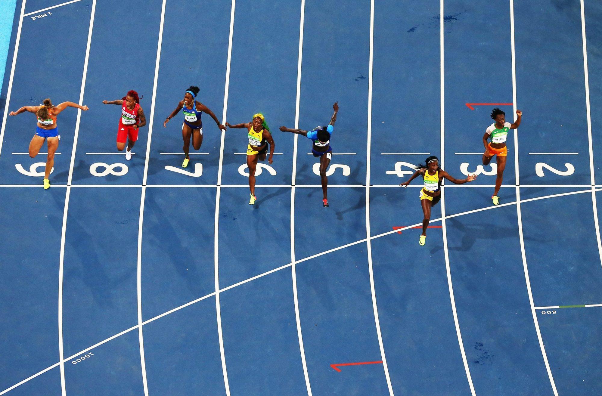 Des athlètes franchissent la ligne d'arrivée d'une course d'athlétisme.