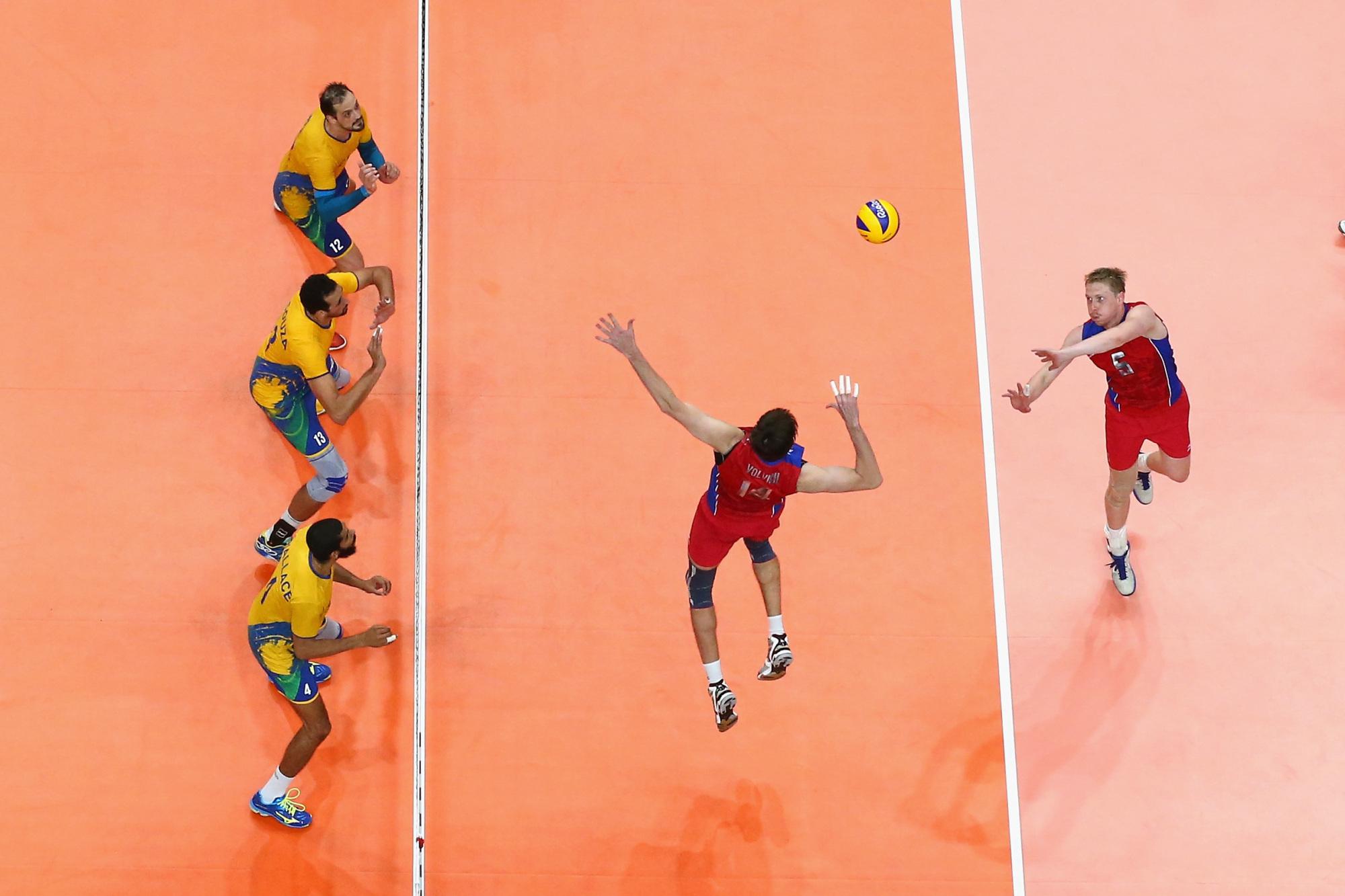 Un joueur de volleyball attaque le ballon près du filet.