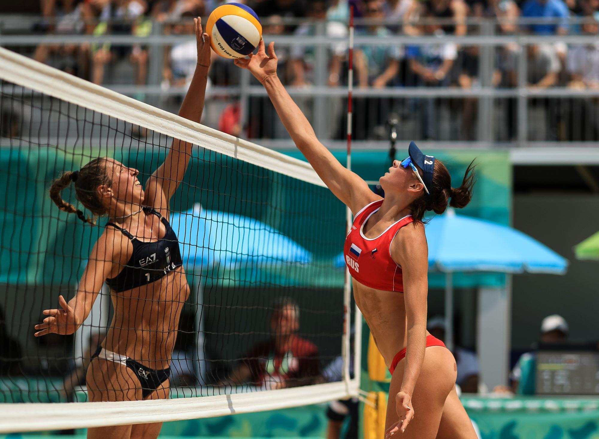 Duel entre deux joueuses de volleyball de plage au filet.