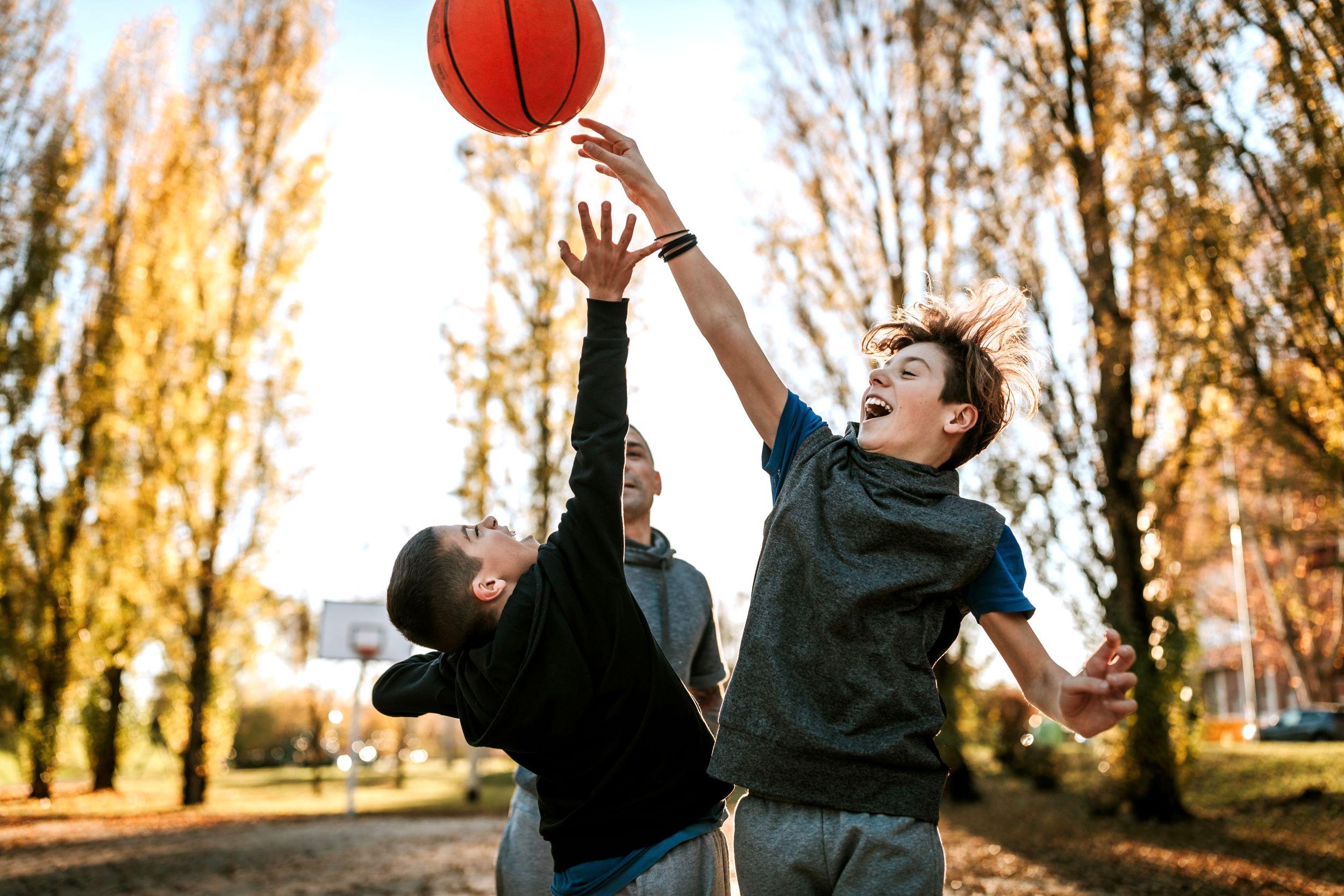 Deux garçons sautent pour attraper un ballon de basket