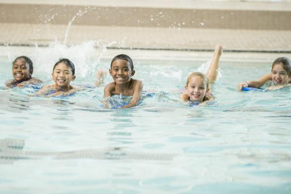 5 enfants nagent dans une piscine