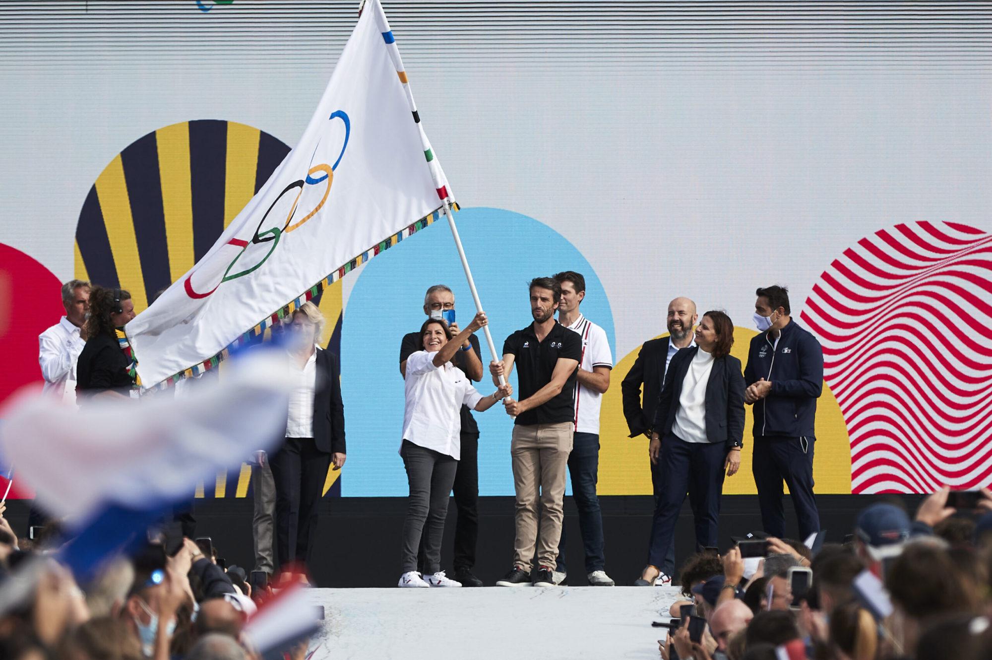 Anne Hidalgo et Tony Estanguet tiennent le drapeau olympique sur une scène, devant la foule
