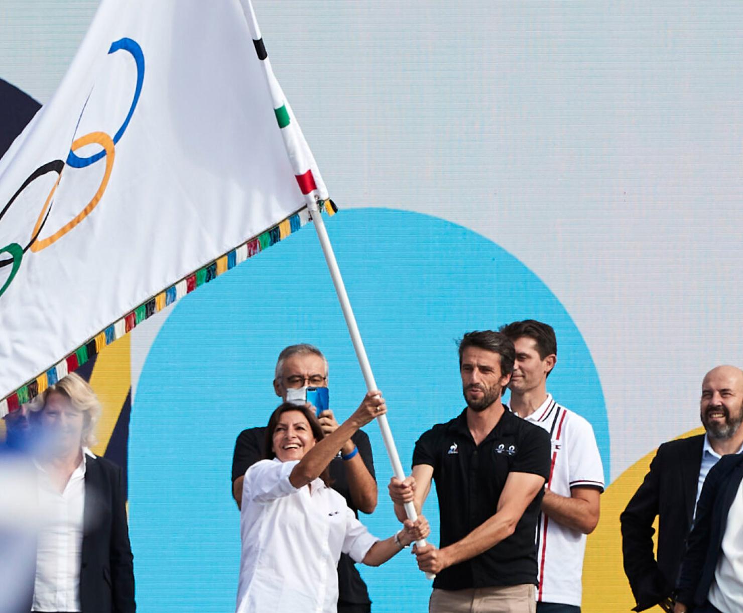 Anne Hidalgo et Tony Estanguet portant le drapeau Olympique